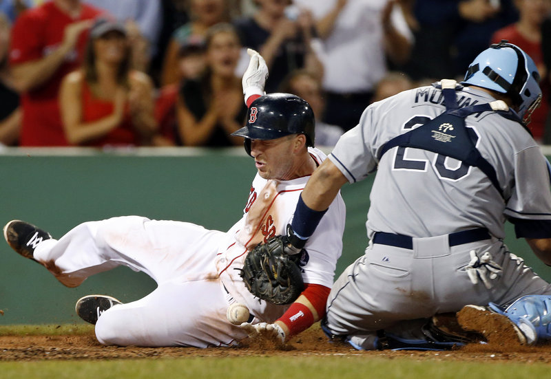 Stephen Drew of the Boston Red Sox slides around Tampa Bay catcher Jose Molina, who couldn't control the ball, to score on Jose Iglesias' eighth-inning single Tuesday night, part of a three-run inning that put away a 6-2 victory at Fenway Park.