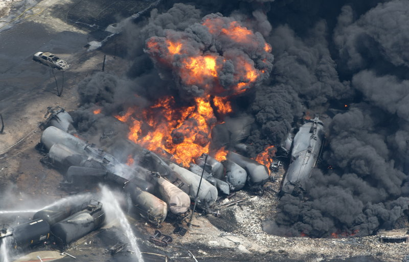 """Smoke rises after railway cars carrying crude oil derailed in Lac-Megantic, Quebec, on July 6. A reader blames the derailment on """"the ridiculously dangerous practice of parking a train on a main running line,"""" rather than on a siding or in a rail yard."""