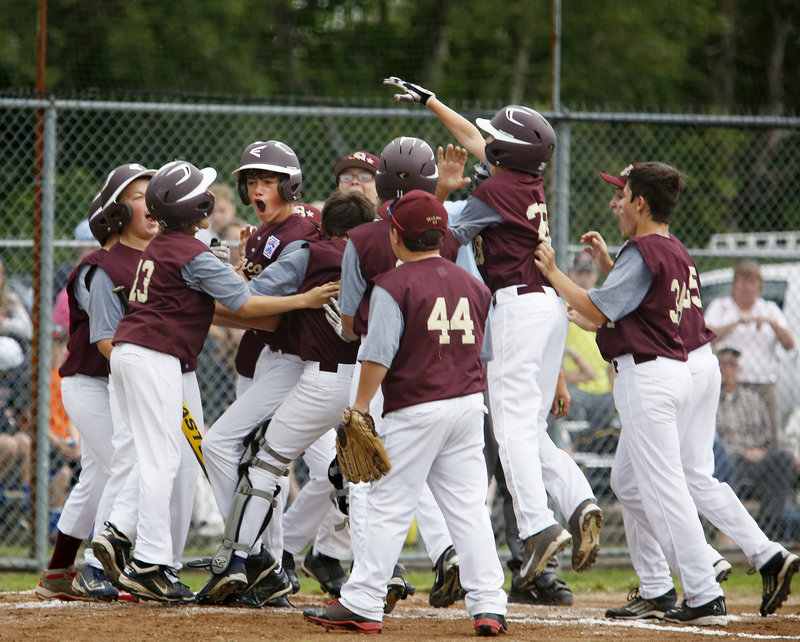 Michael Bourgault of Saco is mobbed by teammates after hitting a three-run homer in the second inning, breaking a tie on the way to a 12-4 win.