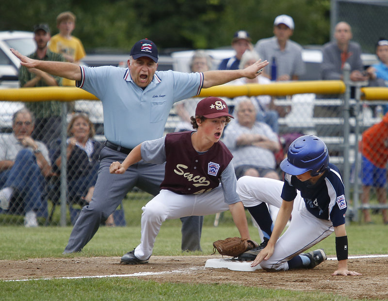Lou Dublin, the third-base umpire, is emphatic with his safe call Thursday night as Owen Burke of Bayside of Portland slides under a tag applied by Michael Bourgault of Saco in the second inning. Saco won 12-4, setting up a final game for the Little League state title.