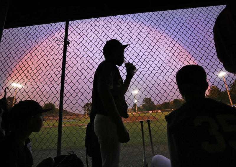 As rain delays the game Thursday night, the Saco Little League baseball players get a chance to admire a colorful sky from their dugout in Augusta during the state-tournament game against Bayside of Portland.