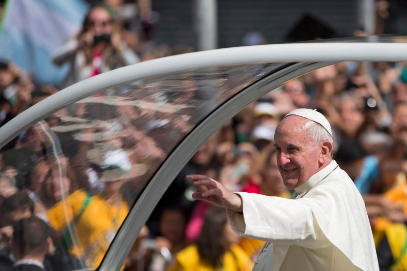 Pope Francis waves from his popemobile as he travels to the archbishop's palace to hold a series of meetings and public noon prayer in Rio de Janeiro, Brazil, on Friday.
