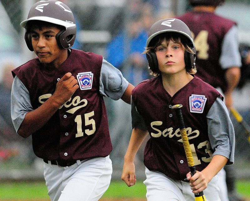 Anthony Bracamonte, left, and Timmy Smith head back the Saco dugout after scoring on Luke Chessie's single in the fourth inning against Bayside.