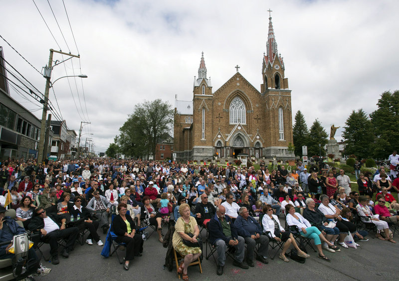 An overflow crowd watches a giant screen outside the Ste-Agnes church during a memorial service on Saturday.