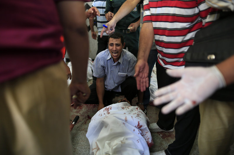 An Egyptian man sits beside his comrade, a supporter of Egypt's ousted President Mohammed Morsi, injured during clashes with security forces in Cairo on Saturday.