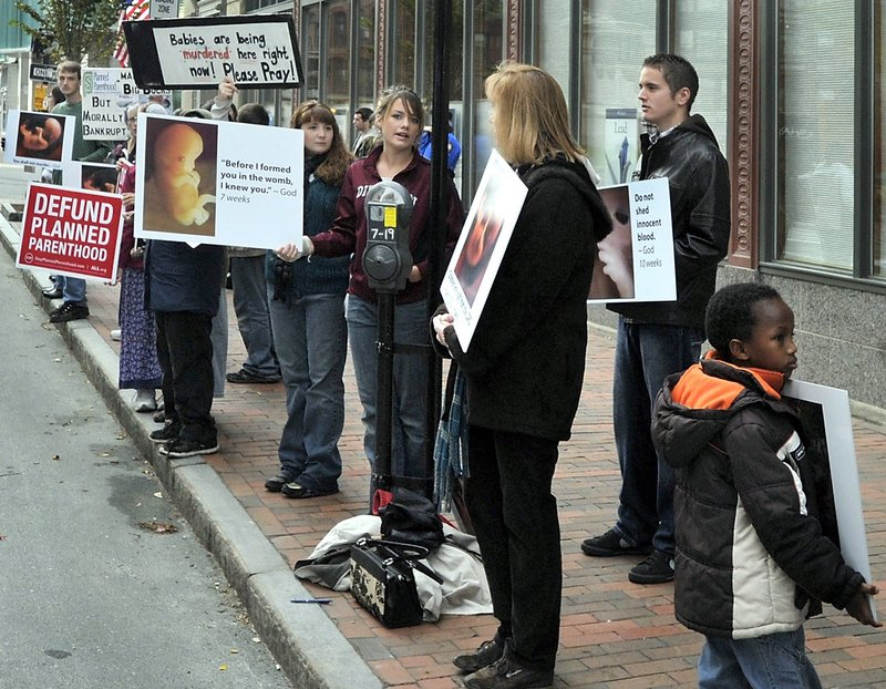 Opponents of abortion protest outside the Planned Parenthood clinic on Congress Street in Portland in an Oct. 19, 2012, file photo. Requiring that the protesters move away from the clinic's door would allow them to show their posters and present their message, while still allowing patients to enter the clinic for medical treatment without being harassed.