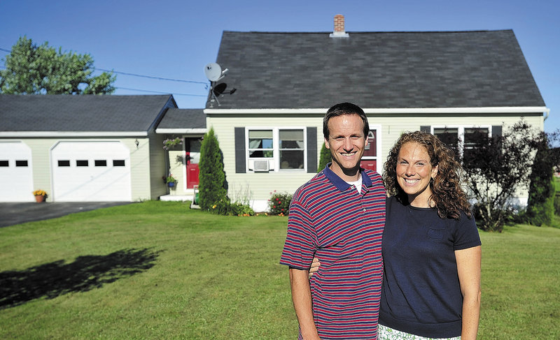 Jeremy and Julie Payne stand in front of their Sidney home. The Paynes are looking to sell their current home and buy a larger one.
