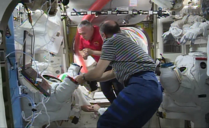 In this screen image from NASA video, astronauts aboard the International Space Station examine the spacesuit that was worn by Italian astronaut Luca Parmitano during a spacewalk that was aborted on Tuesday.