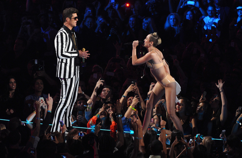 Robin Thicke and Miley Cyrus, wearing a flesh-colored bikini, perform