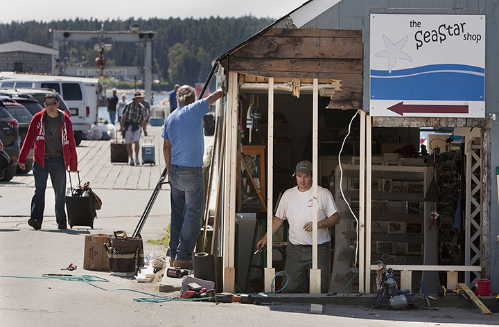 In this Aug. 12, 2013, photo, workers repair damage to a shop at the scene of a fatal auto accident on the wharf in Port Clyde. The accident that killed a 9-year-old boy took place the day before.