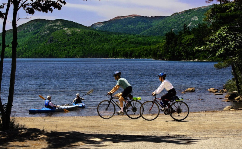 """Bikers cruise along a path while kayakers set off by Eagle Lake in Acadia National Park on Mt. Desert Island, Maine, in this Tuesday, June 21, 2005 file photo. Mount Desert Island, which is linked to mainland Maine by a two-lane bridge, is ranked 25th in Travel & Leisure magazine's article, """"World's Best Islands."""