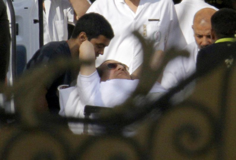Medics escort former Egyptian President Hosni Mubarak, 85, into an ambulance after he was flown by a helicopter ambulance to the Maadi Military Hospital from Tora prison in Cairo on Thursday.