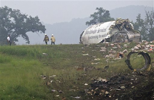Fire crews investigate where a UPS cargo plane lies on a hill at Birmingham-Shuttlesworth International Airport after crashing on approach Wednesday in Birmingham, Ala.