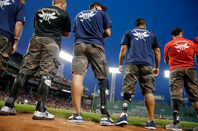 In this Aug. 18, 2013 file photo, members of the Wounded Warrior Amputee Softball Team, made up of active soldiers and veterans who were wounded in service, are given recognition prior to a baseball game between the Boston Red Sox and New York Yankees at Fenway Park in Boston. (AP Photo/Michael Dwyer)