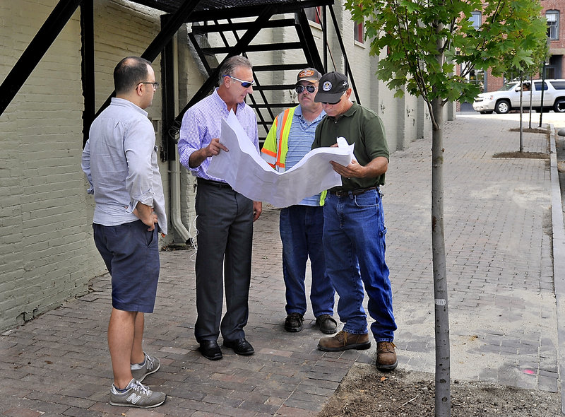 Baxter Academy's chief operating officer Adam Burke, left, looks on Wednesday, Aug. 28, 2013 as general contractor Dan LaBrie of Rufus Lumber, owner of the property, second from left, discusses the completion of improvements to the property with Phil DePierro of the Portland Planning Department, right, and Greg Vining from Public Services, third from left.