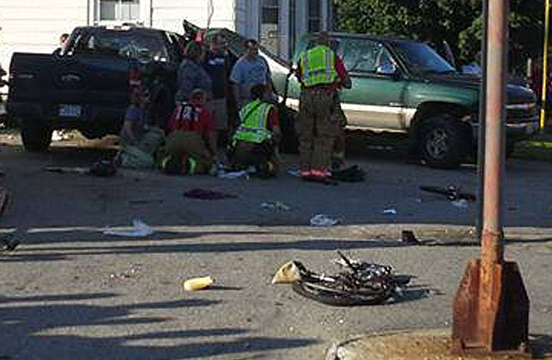 Rescuers attend to one of the victims at the scene of the crash in Biddeford on Friday. David LaBonte's Ford F-150 truck is at left and one of the bicycles lies in the foreground.
