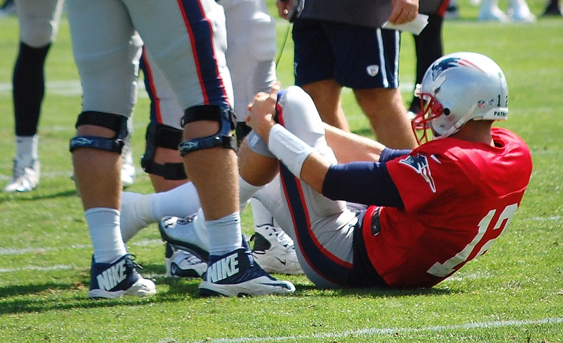 New England Patriots quarterback Tom Brady grabs his left knee after an apparent injury during a joint workout with the Tampa Bay Buccaneers at NFL football training camp in Foxborough, Mass., on Wednesday.