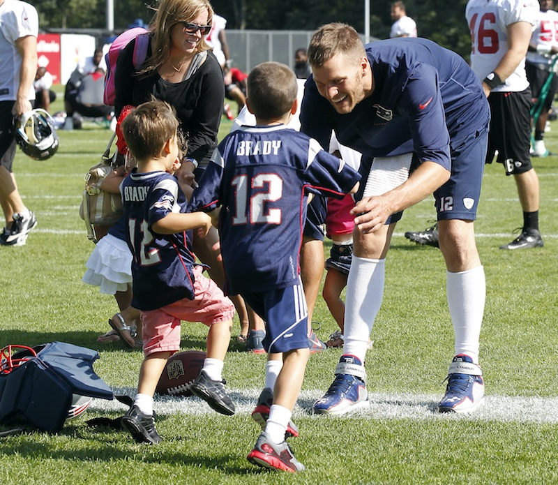 Tom Brady waits as his sons, John Moynahan, center, and Benjamin Brady, left, run to him following the Patriots' joint workout with the Tampa Bay Buccaneers on Thursday.