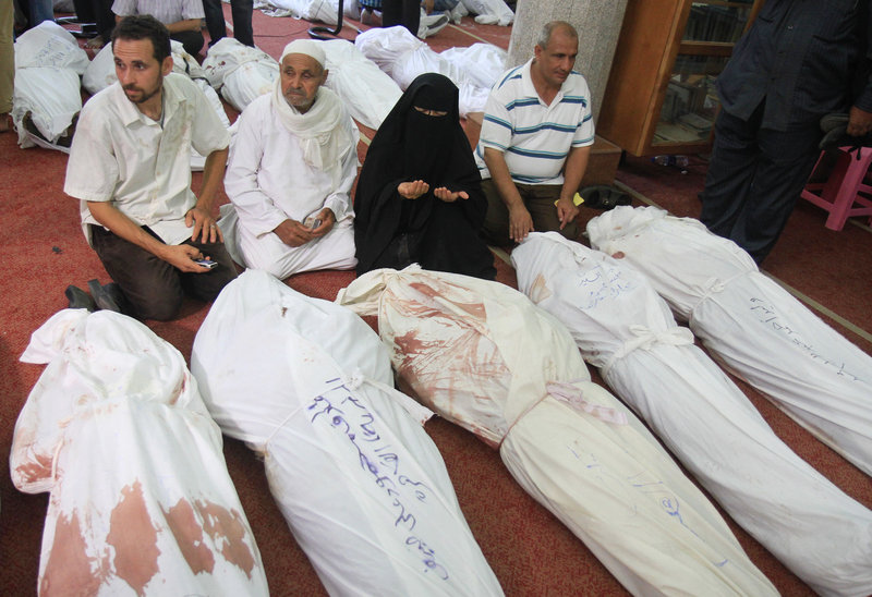 People mourn sitting next to bodies of supporters of ousted President Mohammed Morsi at the El-Iman mosque in Cairo's Nasr City, Egypt, Thursday, Aug. 15, 2013. Egyptian authorities on Thursday significantly raised the death toll from clashes the previous day between police and supporters of the ousted Islamist president, saying hundreds of people died and laying bare the extent of the violence that swept much of the country and prompted the government to declare a nationwide state of emergency and a nighttime curfew. (AP Photo/Ahmed Gomaa)