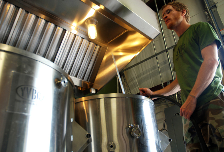Neil McCanon, an Iraq War veteran and head brewer at Young Veterans Brewing Co., adds water to the brew kettle as he prepares to brew Pineapple Grenade Hefeweizen at the Virginia Beach, Va., brewery.