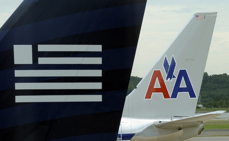 A US Airways, foreground, and an American Airlines plane are seen parked at the terminal at Washington's Ronald Reagan National Airport, Tuesday, Aug. 13, 2013. The Justice Department and a number of U.S. state attorneys general on Tuesday challenged a proposed $11 billion merger between US Airways Group Inc. and American Airlines' parent company, AMR Corp. (AP Photo/Susan Walsh)