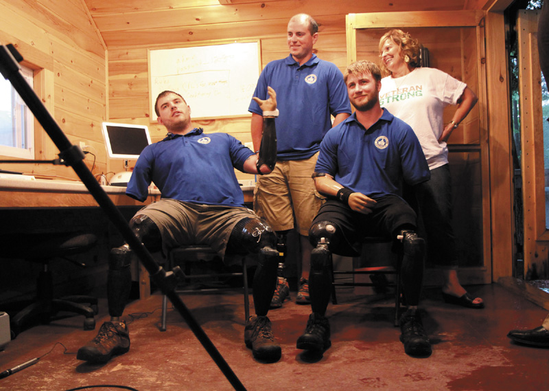 Quadruple amputee Travis Mills, left, talks to reporters with fellow wounded veterans Taylor Morris, right, and Drew Mullee, top, as Maine's First Lady Ann LePage looks on at Camp Kennebec in Belgrade on Wedneday night. This week is