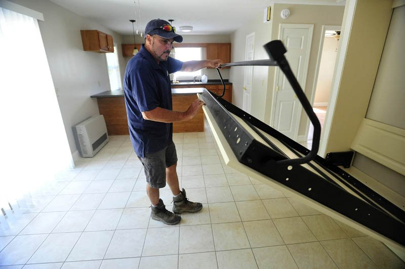 Andy Vear demonstrates how the Murphy bed pulls out to accommodate guests in the combined kitchen, dining and living area at the 20 Cool St. micro-home in Waterville. The main bedroom is through the door to the right and next to that is a full bathroom.