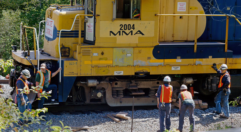 A crew from Montreal, Maine & Atlantic Railway works to put a derailed locomotive back on the tracks in Brownville on Wednesday, July 31, 2013. The Maine-based company filed for bankruptcy Wednesday, Aug. 7, 2013, just 33 days after one of its unattended trains rolled down a hill and derailed, causing explosions that killed 47 people in Lac-Megantic, Quebec.