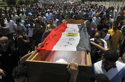 Supporters of Egypt's ousted President Mohammed Morsi march towards Old Cairo carrying the coffin, covered with a national flag, of a colleague who was killed during Wednesday's clashes.