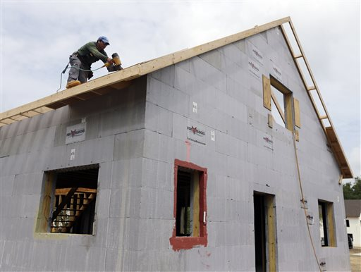 In this July 9, 2013, photo, a construction worker installs a roof on a new home in New Paltz, N.Y.