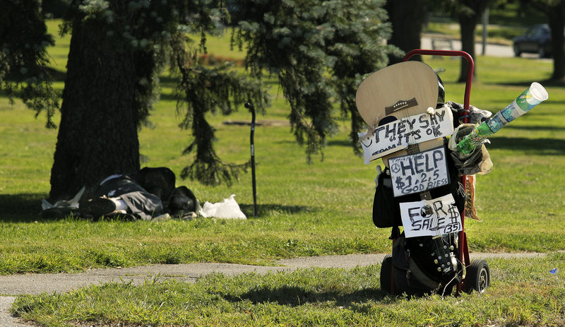 A homeless man named Joe, who declined to give his last name, sleeps in the shade in Deering Oaks Park on Friday, August 16, 2013, behind his prop to collect change at the corner of Marginal Way and Forest Avenue. Joe made the prop in response to the city's new ordinance that prohibits panhandling in medians.