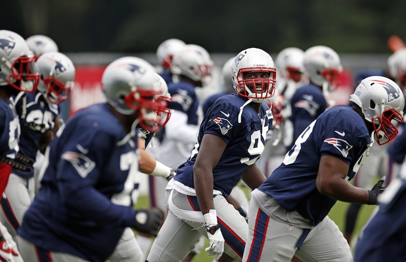 New England Patriots defensive end Chandler Jones laughs with teammates as they jog during team football practice in Foxborough, Mass., Monday, Aug. 26, 2013. (AP Photo/Elise Amendola)