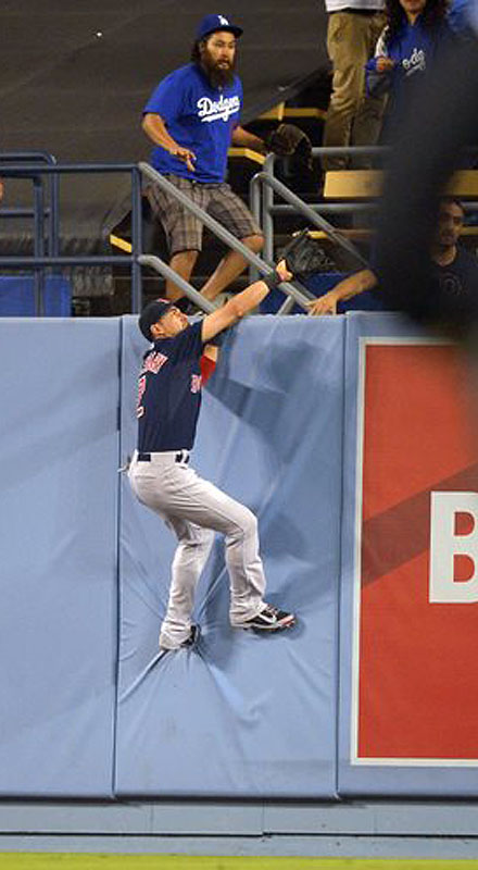 Red Sox center fielder Jacoby Ellsbury climbs the wall as he tries to catch a ball hit for a two-run home run by the Dodgers' Hanley Ramirez in the fourth inning Friday in Los Angeles.
