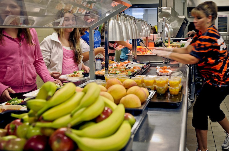 In this Tuesday, Sept. 11, 2012 file photo, students are given healthy choices on a lunch line at Draper Middle School in Rotterdam, N.Y. After just one year, some schools across the nation are dropping out of what was touted as a healthier federal lunch program, complaining that so many students refused the meals packed with whole grains, fruits and vegetables that their cafeterias were losing money. (AP Photo/Hans Pennink, File)