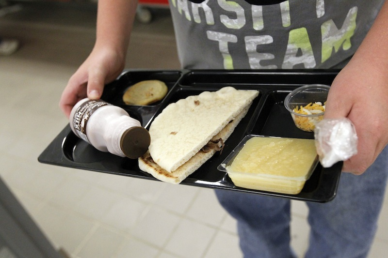 In this Wednesday, Sept. 12, 2012 file photo, a student at Eastside Elementary School in Clinton, Miss., holds a school lunch served under federal standards, consisting of a flatbread roast beef sandwich, apple sauce, chocolate milk and a cookie. After just one year, some schools across the nation are dropping out of what was touted as a healthier federal lunch program, complaining that so many students refused the meals packed with whole grains, fruits and vegetables that their cafeterias were losing money. (AP Photo/Rogelio V. Solis, File)