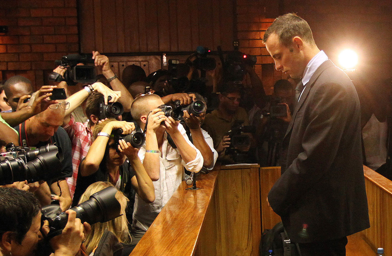 Photographers take pictures of Olympic athlete Oscar Pistorius in February as he stands in the dock during a bail hearing in Pretoria, South Africa.