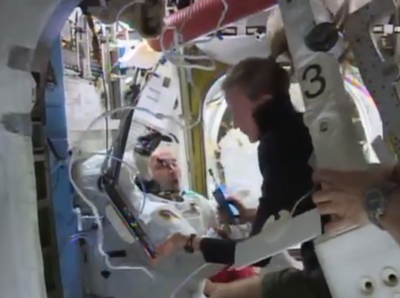 Astronaut Karen Nyberg helps astronaut Luca Parmitano remove his space suit aboard the International Space Station after the aborted spacewalk on July 16, when a dangerous water leak in Parmitano's helmet drenched his eyes, nose and mouth, preventing him from hearing or speaking.