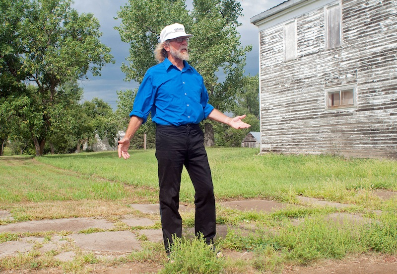In this Aug. 26, 2013, photo Craig Cobb stands in an empty lot he owns on Main Street in Leith, N.D., where he envisions a park _ perhaps with a swimming pool _ dedicated to the late neo-Nazi and white supremacist activist William L. Pierce. Cobb, 61, a self-described white supremacist, has purchased about a dozen lots in Leith and over the past year he has invited fellow white supremacists to move there and help him to transform the town of 16 people into a white enclave. No one has come, but the community is mobilizing to fight out of fear that Cobb could succeed, and the mayor has vowed to do whatever it takes to ensure Cobb's dream remains just that. (AP Photo/Kevin Cederstrom)