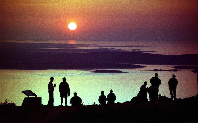 """In this September 1999 file photo, visitors to Acadia National Park watch the sunrise from the summit of Cadillac Mountain near Bar Harbor, Maine, one of the first places on the East Coast to see the sun appear. Mount Desert Island, which is linked to mainland Maine by a two-lane bridge, is ranked 25th in Travel & Leisure magazine's article, """"World's Best Islands."""