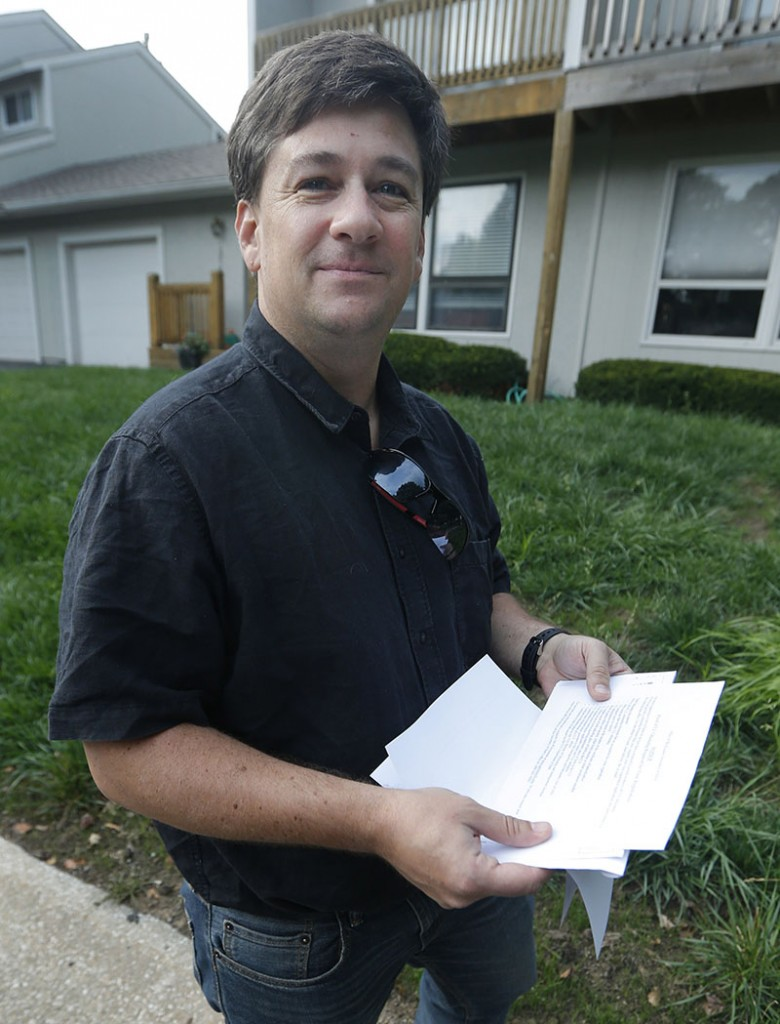 Aaron Belenky holds a letter from election officials while standing in front of his apartment in Overland Park, Kan., Wednesday, Aug. 14, 2013. Belenky allowed the American Civil Liberties Union to list him as one of three aggrieved voters in a notice sent this week to Kansas Secretary of State Kris Kobach.