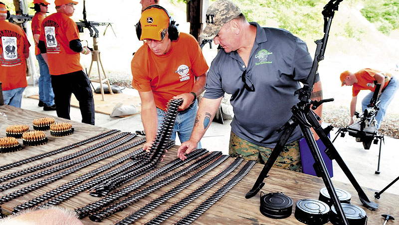 Andy Williams, right, and a volunteer load automatic weapons with live ammunition belts during the Wounded Warrior Machine Gun Shoot in North Anson on Sunday.