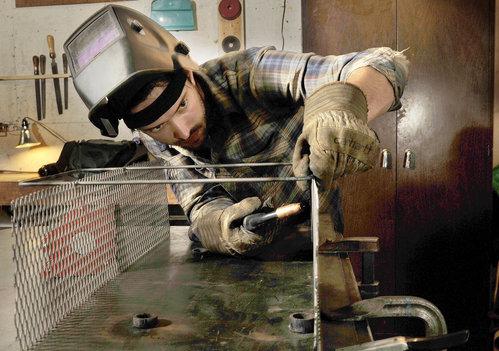 Metal fabricator John Nelson welds a basket at his Portland shop.