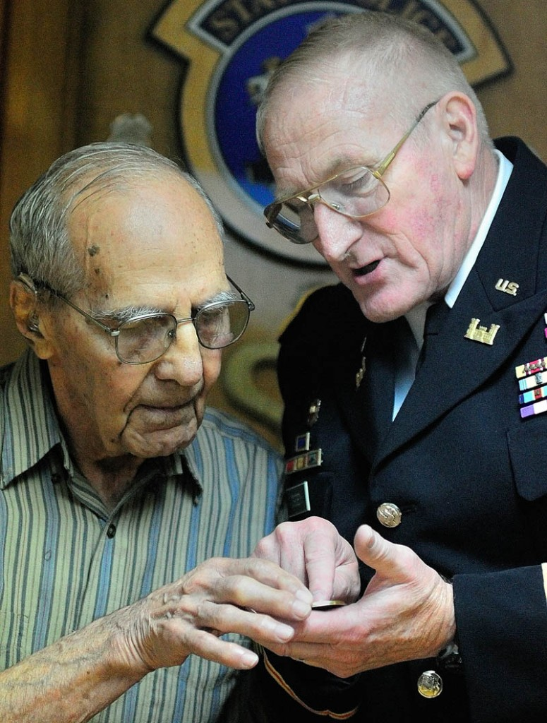 World War II veteran Al Kramer, of South China, left, and Peter W. Ogden, Director of the state's Bureau of Veterans' Services, look at a commemorative coin given to Kramer by Ogden during a cermeony on Thursday August 29, 2013 from Rep. Mike Michaud in Augusta.