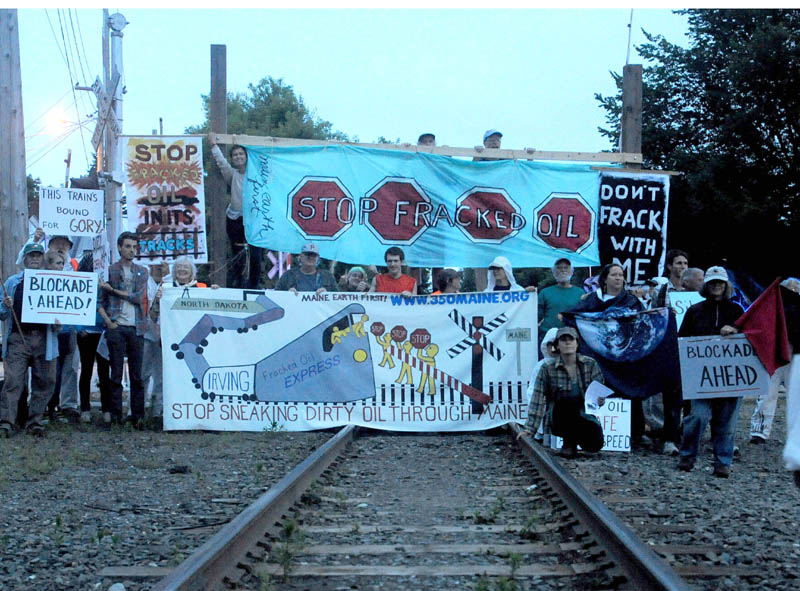 Protesters from 350 Maine and Earth First, block the railroad track crossing at Lawrence Avenue in Fairfield in June to protest the transport of tracked oil on railroads.
