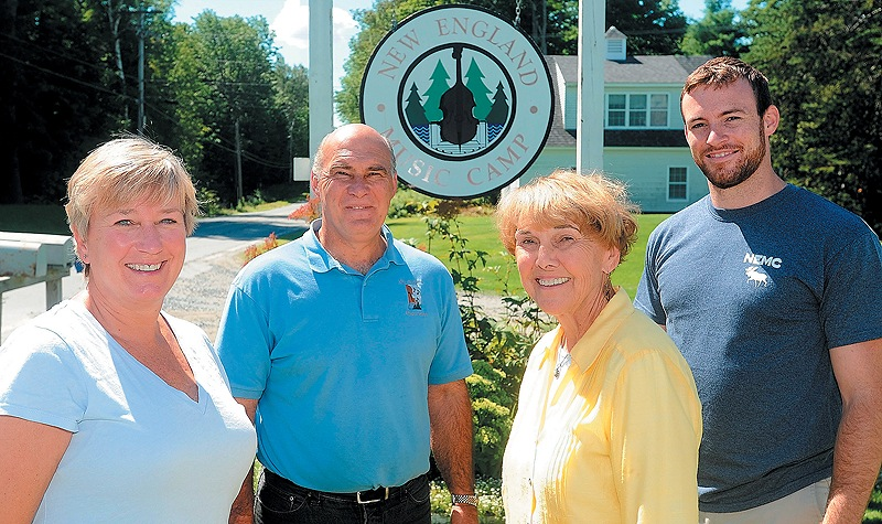 Jeanette Wiggin, director emeritus, grandson Matthew, right, son John and daughter-in-law Kim, left, stand at the entrance to the New England Music Camp in Sidney. The family hopes wealthy donors will fund the camp's expansion.