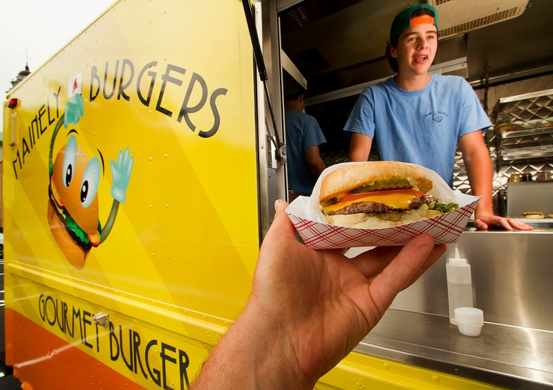 Mainely Burgers attendant Jackson Berman chats with a customer at the lunch wagon in Portland.