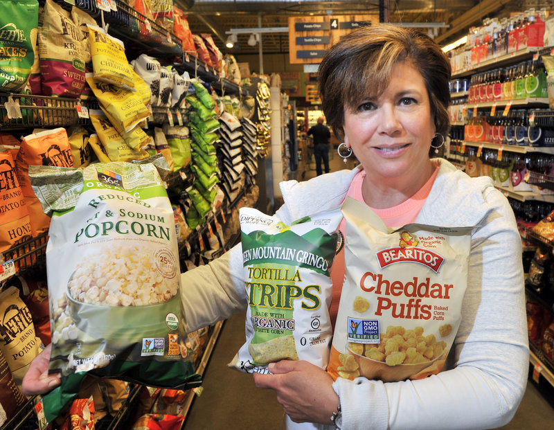 Barbara Gulino of Whole Foods in Portland holds some of the hundreds of products with labels indicating they're non-genetically modified, certified organic or locally produced.