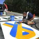 """Matt Tobin and Jeremy Gardner paint the starting line area on Route 77 in Cape Elizabeth on Wednesday morning in preparation for Saturday's Beach to Beacon road race. The """"Boston Strong"""" ribbon is an addition this year to support the city and the marathon bombing victims."""