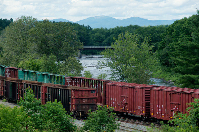 """Boxcars owned by the Montreal, Maine & Atlantic Railway sit idle next to the Pleasant River in Brownville last Tuesday. The cars still carry the """"BAR"""" markings of the Bangor and Aroostook Railroad, which operated between 1891 and 1995. A significant part of the company's business was hauling potatoes from Aroostook County in heated boxcars."""