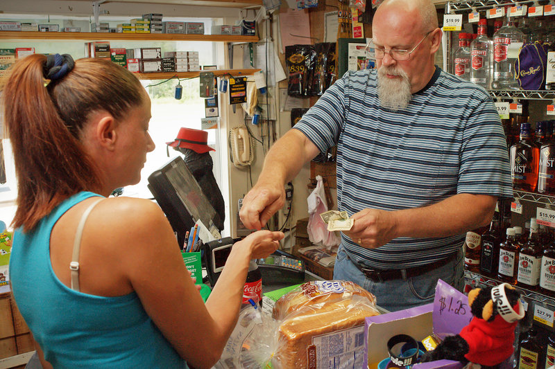 """Steve Johnson, above, owner of the General Store & More on Route 11 in Brownville, makes change for Tammy Laythe on Wednesday. Johnson said revenue at the store has fallen. """"Everything has slowed down a bit,"""" he said."""